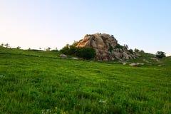 Der Flusssteinfelsen auf dem Wiesensonnenuntergang Lizenzfreie Stockfotografie