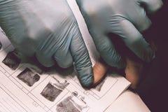 Der Forscher nimmt Fingerabdrücke vom Verdächtigen im Verbrechen Untersuchung ist ein Verbrechen verbrechen Stockbilder