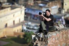 Der Fotograf, der hoch auf einem Felsen über den Häuserblöcken sitzt und entfernt indische Stadt stockfotografie