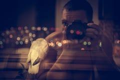 Der Fotograf, der Inspirationsfoto des Vogels mit Nachtstadt macht, beleuchtet auf Hintergrund stockfotografie