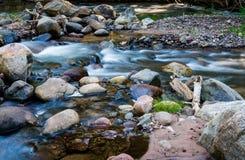 Der Frühlings-Nebenfluss, der mit Felsen fließt, bedecken kleine Stromschnellen mit Gras stockbild