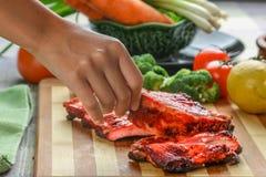 Der Frau pflücken herauf ein BBQ-Schweinsrippchen mit der Hand Lizenzfreie Stockfotos