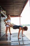 Der Fraueneignungslehrer, der junge Frau in der Übung unterstützt, übertreffen Stockbilder