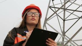 Der Fraueningenieur, der nahe einer elektrischen Nebenstelle arbeitet, zeichnet, Stromleitungen, Teamwork stock footage