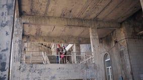 Der Fraueningenieur und der Vorarbeiter im Sturzhelm vergleichen die Aussage, die für Baumaterialien erworben wird und bestätigen stock video
