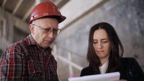 Der Fraueningenieur und der Vorarbeiter im Sturzhelm vergleichen die Aussage, die für Baumaterialien erworben wird und bestätigen stock footage