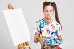 der Frauenmaler, der in der bunten Farbe beschmutzt wird, zeichnet auf Segeltuch Stockfotografie