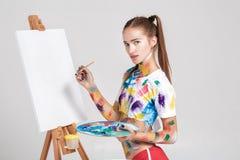 der Frauenmaler, der in der bunten Farbe beschmutzt wird, zeichnet auf Segeltuch Stockfoto