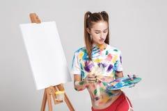 der Frauenmaler, der in der bunten Farbe beschmutzt wird, zeichnet auf Segeltuch Lizenzfreie Stockfotos