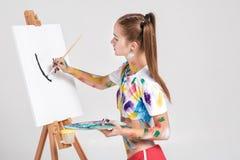 der Frauenmaler, der in der bunten Farbe beschmutzt wird, zeichnet auf Segeltuch Stockbild