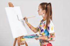 der Frauenmaler, der in der bunten Farbe beschmutzt wird, zeichnet auf Segeltuch Stockfotos