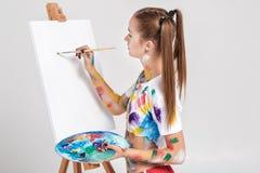 der Frauenmaler, der in der bunten Farbe beschmutzt wird, zeichnet auf Segeltuch Lizenzfreie Stockbilder