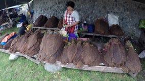 Der FrauenStraßenhändler, der breiten getrockneten Tabak verkauft, verlässt auf der Straßenseite stock footage