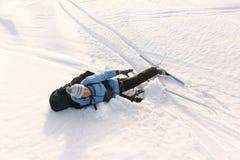 Der Frauentourist mit einem Rucksack, der auf Schnee liegt Stockfoto