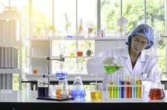 Der Frauenwissenschaftler, der Experiment im Labor tut, das Aufflackernlicht haben stockfoto