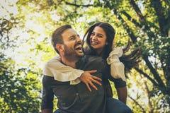 Der Freund, der seine Freundin tragen trägt an huckepack Porträt lizenzfreies stockfoto
