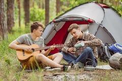 Der Freund zwei, der im Zelt sitzt, spielen die Gitarre und singen Lieder Stockfoto