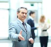 Der freundliche Geschäftsmann, der zum Händedruck mit der verlängerten Hand bereit ist, arbeiten vor dem hintergrund der Arbeit s lizenzfreie stockfotografie