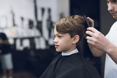 Der Friseur macht eine moderne hübsche Frisur für den Jungen in einem modernen Friseursalon Lizenzfreies Stockbild