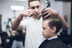Der Friseur macht eine moderne hübsche Frisur für den Jungen in einem modernen Friseursalon Lizenzfreie Stockbilder