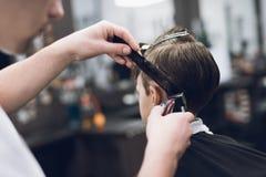 Der Friseur macht eine moderne hübsche Frisur für den Jungen in einem modernen Friseursalon Lizenzfreies Stockfoto