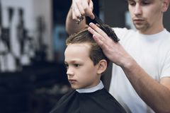 Der Friseur macht eine moderne hübsche Frisur für den Jungen in einem modernen Friseursalon Lizenzfreie Stockfotografie