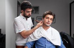 Der Friseur rasiert den Bart des Kunden mit Rasiermesser Lizenzfreie Stockbilder