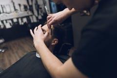 Der Friseur rasiert seinen Kopf, Schnurrbart und Bart zum Mann im Friseursalon Lizenzfreie Stockbilder