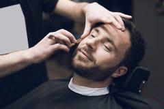 Der Friseur rasiert seinen Kopf, Schnurrbart und Bart zum Mann im Friseursalon Stockfoto