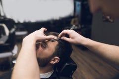 Der Friseur rasiert seinen Kopf, Schnurrbart und Bart zum Mann im Friseursalon Stockbilder