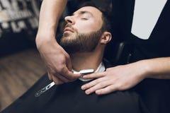 Der Friseur rasiert seinen Kopf, Schnurrbart und Bart zum Mann im Friseursalon Stockbild