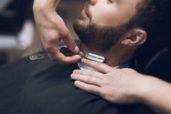Der Friseur rasiert seinen Kopf, Schnurrbart und Bart zum Mann im Friseursalon Stockfotografie