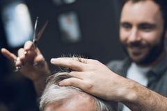 Der Friseur tut eine Frisur einen alten Mann mit dem grauen Haar in einem Friseursalon an Lizenzfreie Stockfotografie