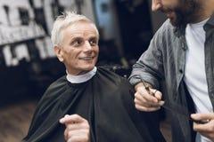 Der Friseur tut eine Frisur einen alten Mann mit dem grauen Haar in einem Friseursalon an Lizenzfreies Stockbild