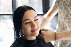 Der Friseur tut einen Haarschnitt mit Scheren des Haares ein junges Mädchen in einem Schönheitssalon an lizenzfreie stockfotos