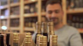 Der frohe Kerl, der einige Flaschen in seinen Händen und gehen nimmt glücklich, weg Kerl, der, den Wein im Speicher zu wählen uns stock video footage