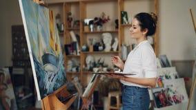 Der frohe weibliche Künstler malt das Bild, das Boot im Meer dann zurücktretend darstellt, ihre Arbeit betrachtend und mit lächel stock video