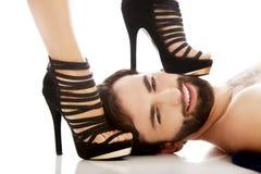 Der Fuß der Frau auf dem Gesicht des Mannes Stockfoto