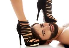 Der Fuß der Frau auf dem Gesicht des Mannes Stockfotos