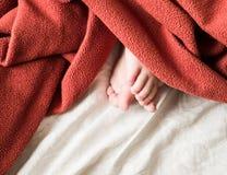 Der Fuß des Babys unter einer Abdeckung Stockfotografie