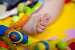 Der Fuß des kleinen Babys unter Spielwaren Stockfoto