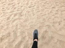 Der Fuß im grauen Stiefelschuh macht einen Schritt vor dem hintergrund eines natürlichen losen gelben goldenen schönen warmen Str lizenzfreies stockbild