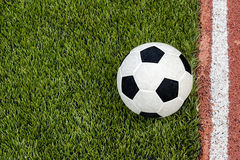 Der Fußball ist nahe der Linie auf dem künstlichen Grasfußballplatz Lizenzfreie Stockfotografie