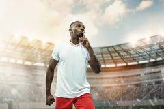 Der Fußballspieler in der Bewegung auf dem Feld des Stadions stockfotografie
