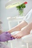 Der Fußpfleger, der anwendet, Nagellack zu den Zehennägeln Pediküre BADEKURORT-PR Lizenzfreie Stockfotos
