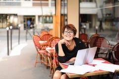 der gealterte weibliche Verfasser, der mit neuem Buch im Laptop arbeitet und haben stockfoto