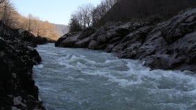 Der Gebirgsfluss, der unter den Felsen läuft stock footage