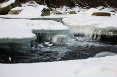 Der Gebirgsfluss läuft schnell unter eine starke Kruste des Eises lizenzfreies stockfoto