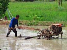 Der Gebrauch der Ackerschlepper auf den thailändischen Reisgebieten in der Regenzeit Lizenzfreies Stockbild
