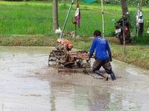 Der Gebrauch der Ackerschlepper auf den thailändischen Reisgebieten in der Regenzeit Stockbild